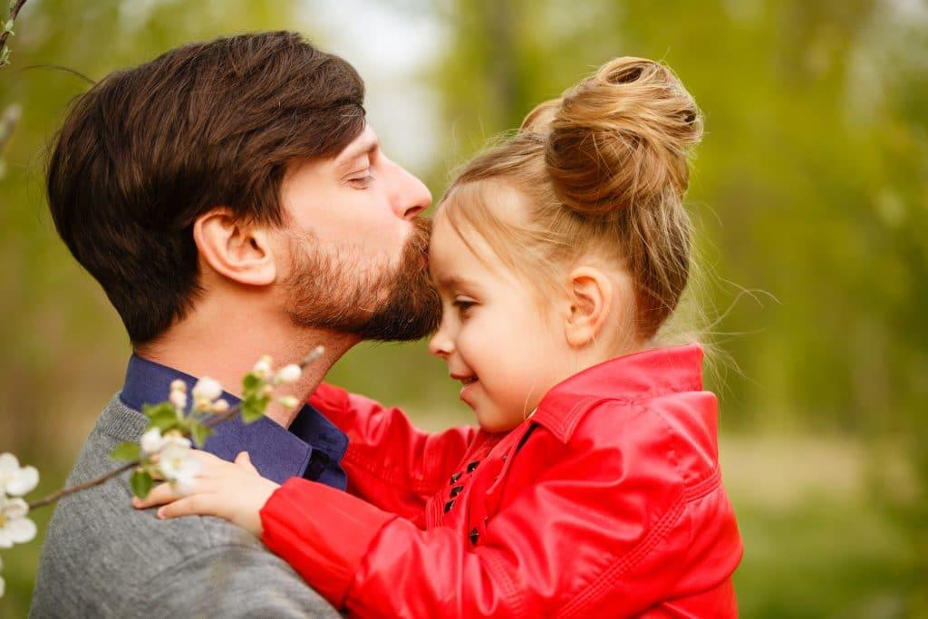 Pai dando um beijo na testa de sua filha em sinal de amor.