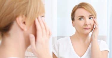 Mulher de meia idade olhando para o seu reflexo no espelho enquanto toca seu rosto, com expressão séria.