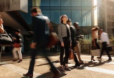 Mulher parada na rua enquanto pessoas passam em volta, em movimento.