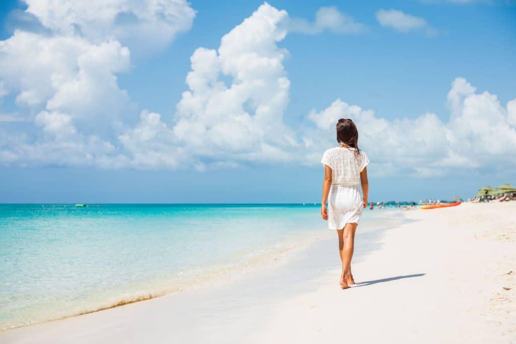 Mulher de costas andando em uma praia de águas azuis.