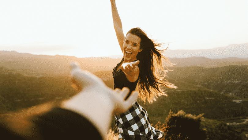 Mulher feliz com a mão estendida nos campos