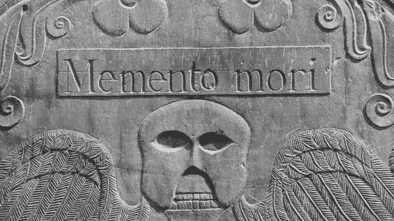"""Lápide com o escrito 'memento mori"""" gravado nela"""