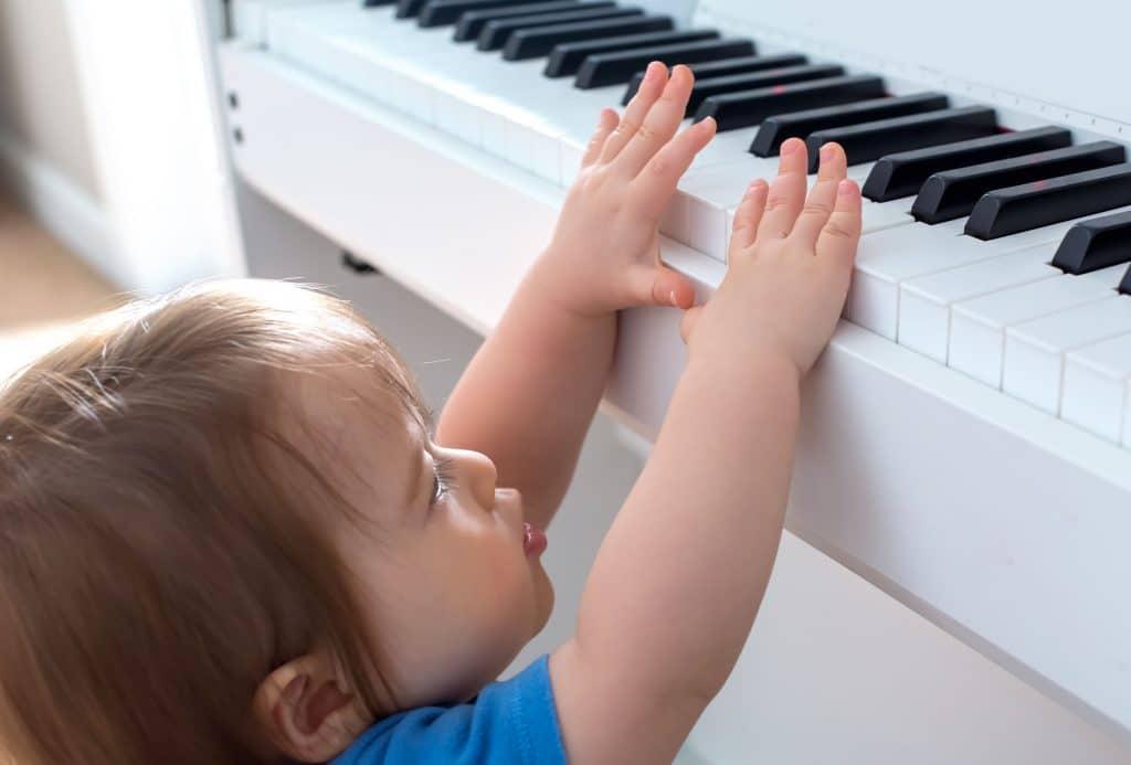 Criança tentando tocar um piano