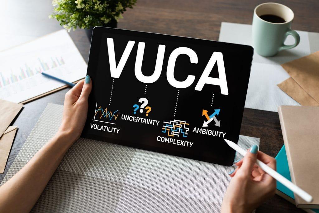 Mulher escrevendo em tablet com caneta própria. Na tela do aparelho, vemos as letras VUCA e desenhos embaixo de cada letra na ordem: um gráfico instável, pontos de interrogação, um labirinto, e setas indicando vários lados.