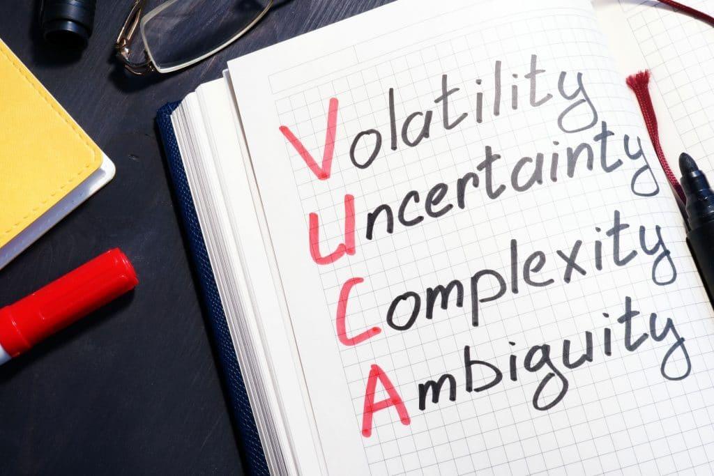 Acrônimo de VUCA escrito em caderno, com as iniciais em vermelho e o resto das palavras em preto.