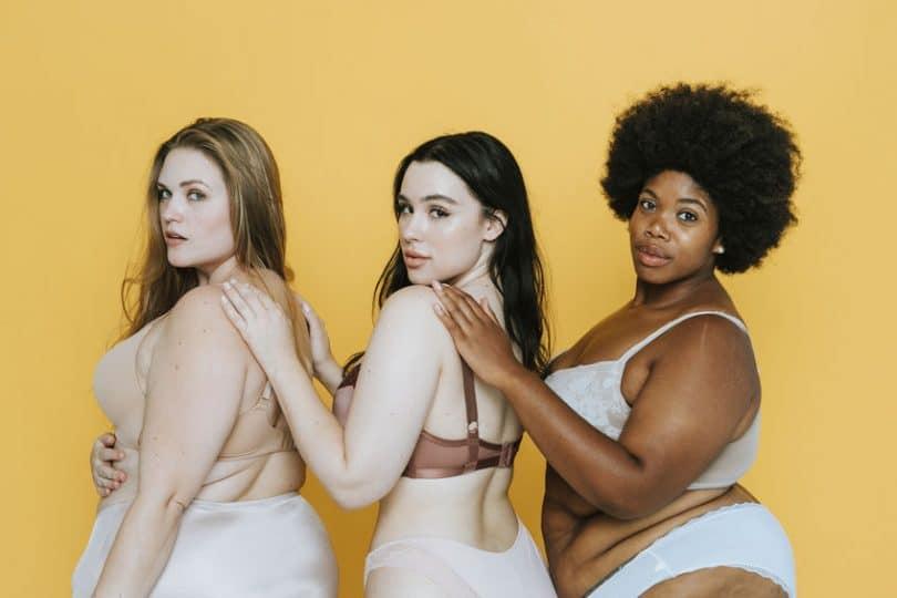 Mulheres de lingerie de costas olhando para trás com fundo amarelo