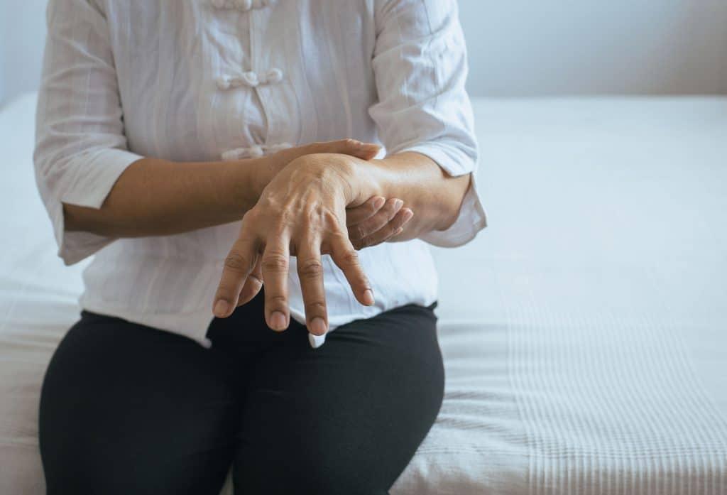 Mulher com mal de parkinson segurando seu braço