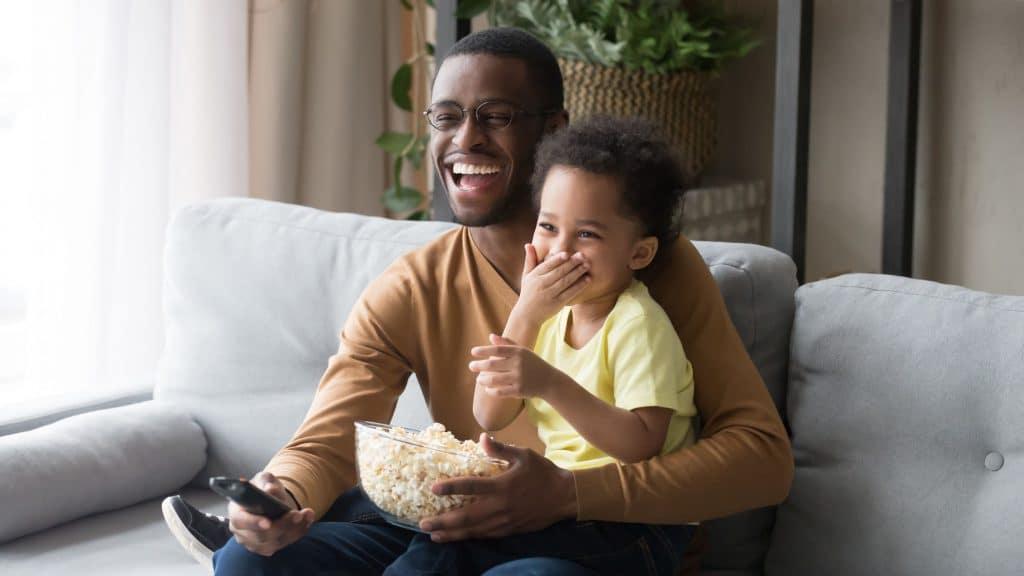 Pai e filho assistindo televisão segurando pipoca