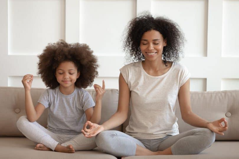 Mãe e filha meditando em sofá