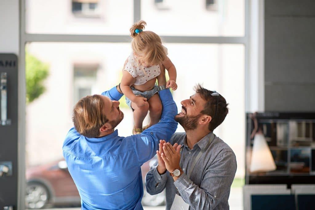 Casal de homens segurando uma criança no alto e sorrindo