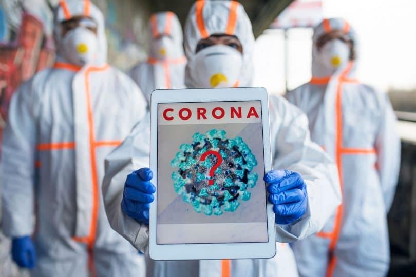 """Grupo de pessoas com roupa de proteção e máscaras, enquanto a pessoa mais a frente segura um tablet com a imagem de um vírus com um ponto de interrogação no centro, e a palavra """"corona"""" no topo da tela."""