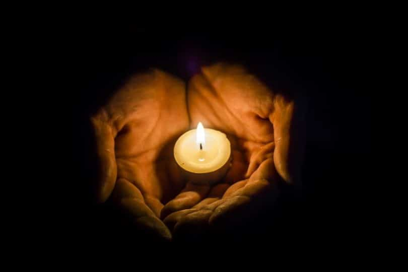 Mãos unidas formando uma concha, segurando uma pequena vela acesa.
