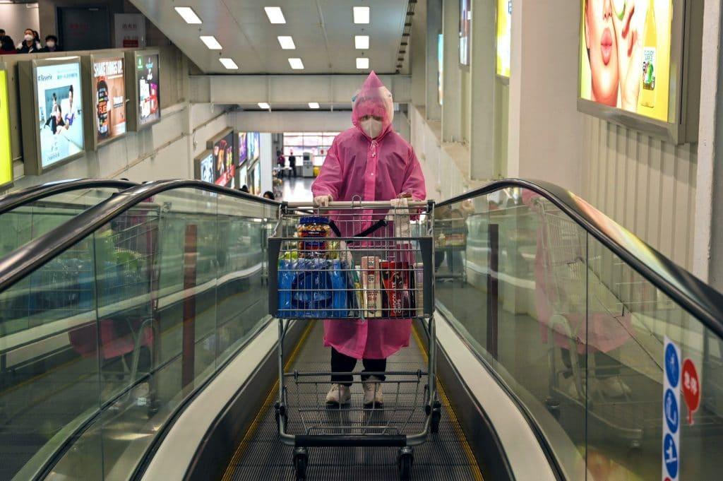 Pessoa usando máscara e capa plástica em um supermercado, com seu carrinho de compras cheio de mantimentos.