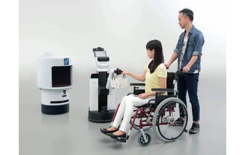 O robô HSR, em formato circular com uma abertura frontal, e o robô DSR, uma pequena torre com uma tela no topo, e um gancho central, que está entregando uma cesta a uma mulher em uma cadeira de rodas.