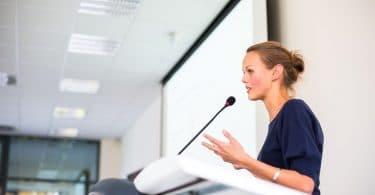 Mulher gesticulando com as mãos enquanto dá um discurso em um pequeno microfone.