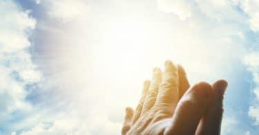 Mãos unidas em sinal de oração, apontando para um céu ensolardo.