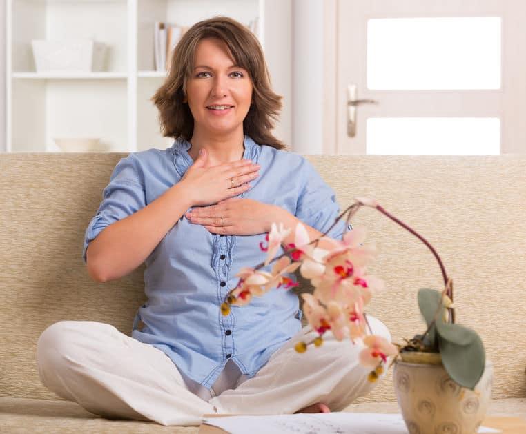 Mulher sentada em sofá com mãos no peito
