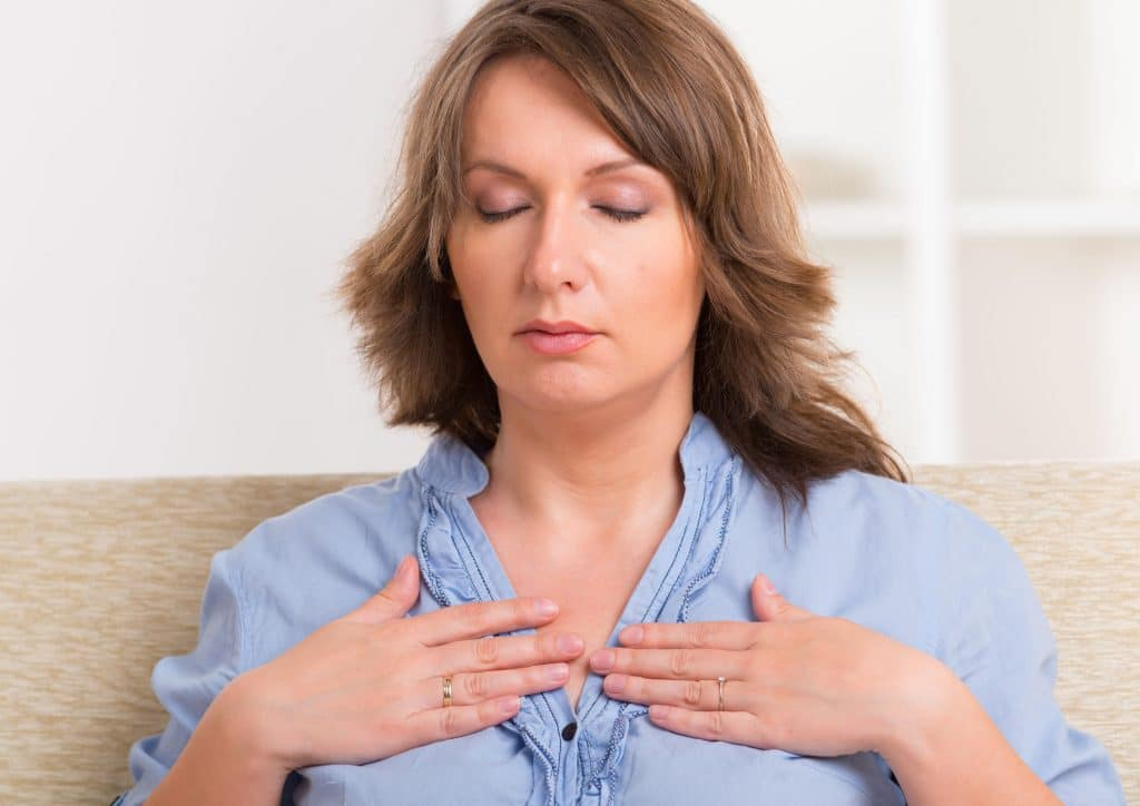 Mulher praticando reiki sozinha