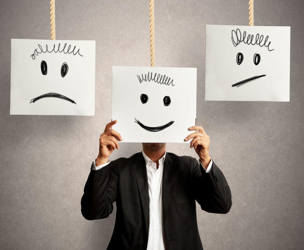 Pessoa segurando uma folha desenhado um sorriso e ao lado outros desenhos de triste e pensativo