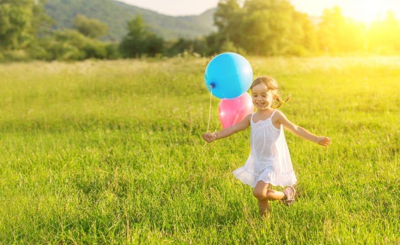 Menina pequena correndo feliz por um campo, enquanto segura balões de aniversário.