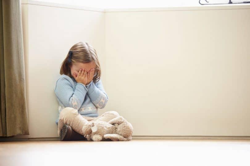 Menina sentada no chão em um canto, cobrindo seu rosto com suas mãos.