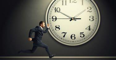 Homem correndo em frente a um relógio gigante em uma parede.