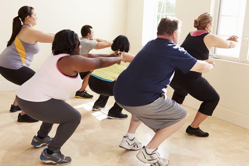 Pequeno grupo de pessoas obesas observando uma treinadora ensinando um exercício enquanto o grupo reproduz.