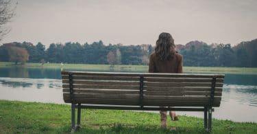 Mulher sentada em um banco, de costas, na beira de um rio.