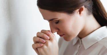 Mulher de olhos fechados e cabeça baixa, com as mãos entrelaçadas em sinal de oração.