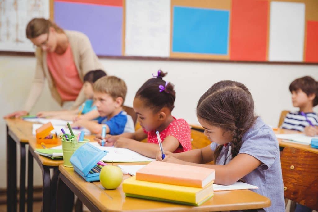 Crianças em escola, sentadas lado a lado, a maioria brancos, com uma menina negra no centro.