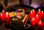 Pequena bola de cristal cercada por velas vermelhas