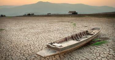 Barco parado sobre o solo seco e rachado, em um sertão.