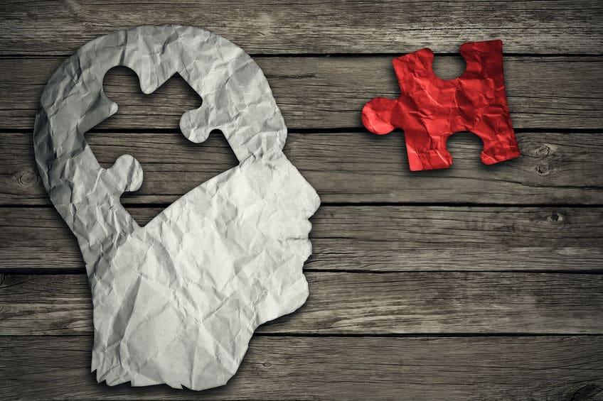 Papel alumínio recortado em formato de cabeça, com um espaço vazio em formato de peça de quebra-cabeça na altura do cérebro. A peça que se encaixa está ao lado, pintada de vermelho.