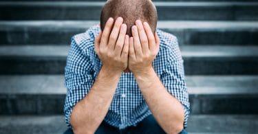 Homem com cabeça abaixada e mãos apoiadas no joelhos