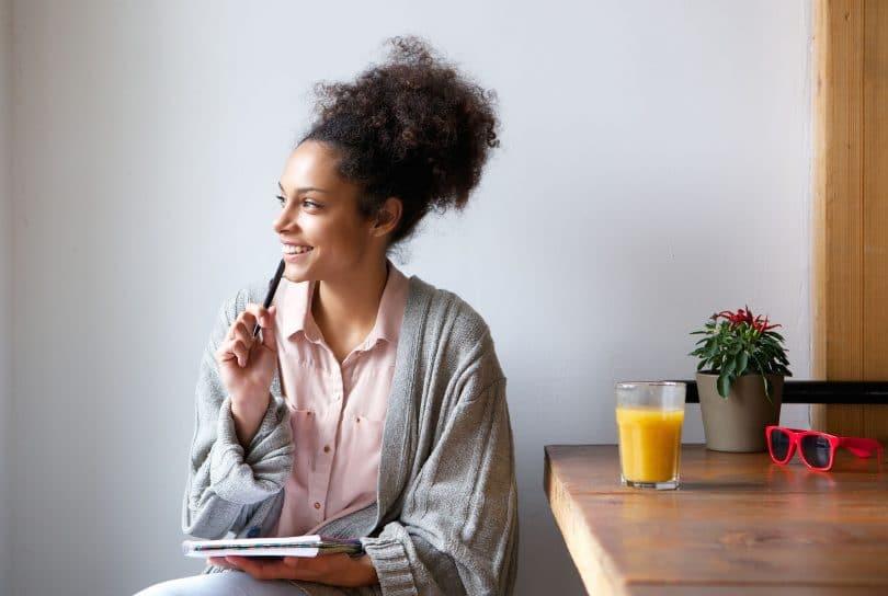 Mulher pensativa sorrindo segurando um caderno