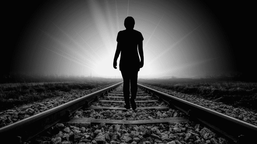 Silhueta de pessoa caminhando nos trilhos do trem em direção a luz
