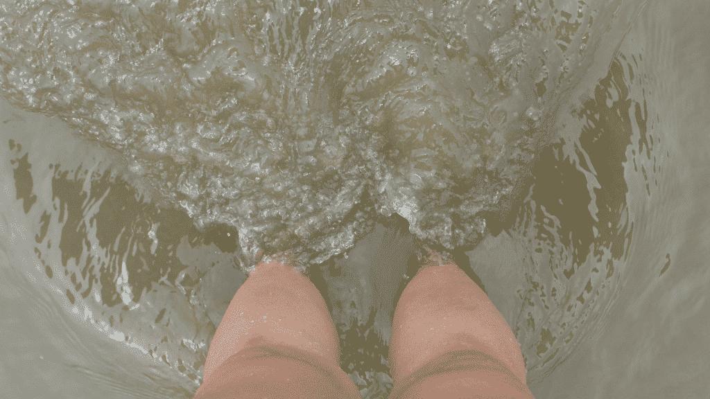 Foto das pernas de uma mulher na água suja