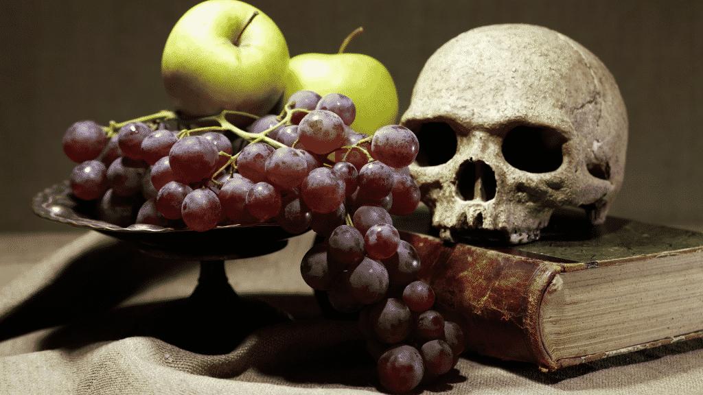 Foto de natureza morta com crânio sobre um livro ao lado de maçãs verdes e uvas