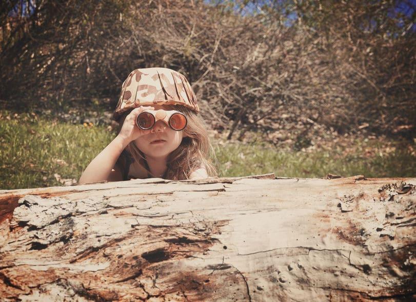 Criança atrás de tronco de árvore com binóculo