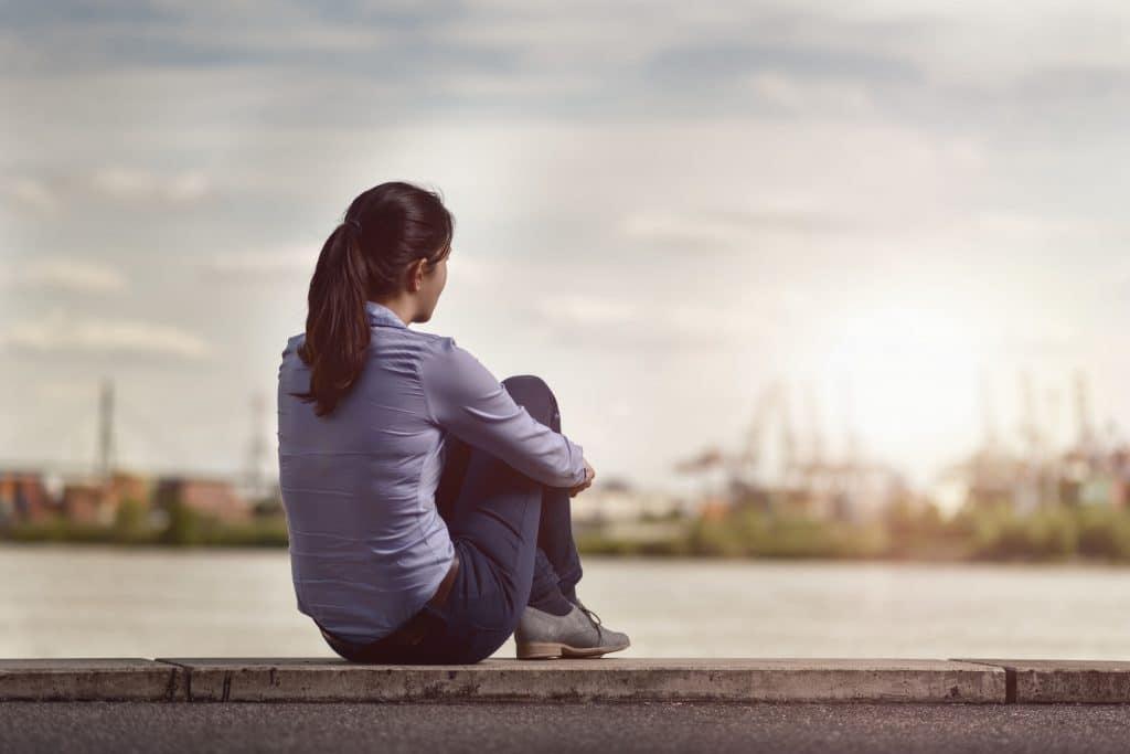 Mulher sentada em um muro olhando para o horizonte pensativa
