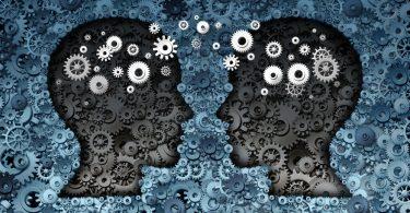 Desenho de duas cabeças sobre engrenagens azuis, e engrenagens brancas saem das cabeças e se encontram no centro da imagem.