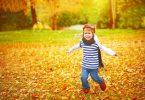 Criança feliz correndo em folhas de outono
