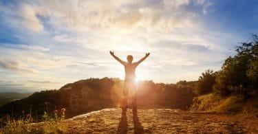 Homem de costas com braços abertos em montanha e céu ao fundo