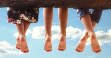 Três crianças sentadas em um tronco com os pés balançando.