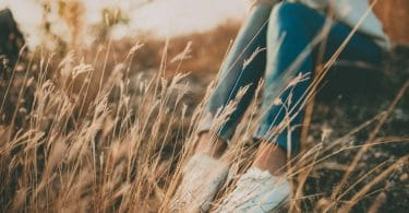 Pessoa sozinha sentada em um gramado com