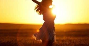 Silhueta de mulher com braços abertos e sol refletindo