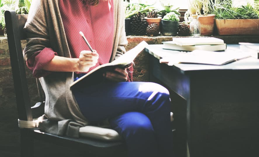 Mulher sentada em uma cadeira, com as pernas cruzadas. Ela escreve em um caderno que segura em seu colo.