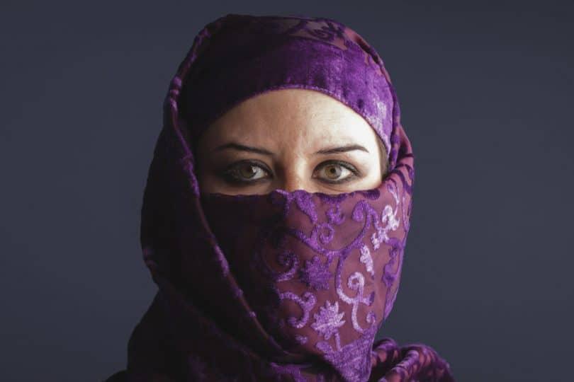 Mulher com burca roxa e olhos verdes abertos