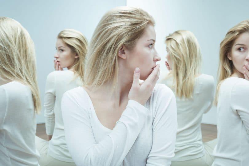 Mulher confusa e assustada em uma sala cheia de espelhos.