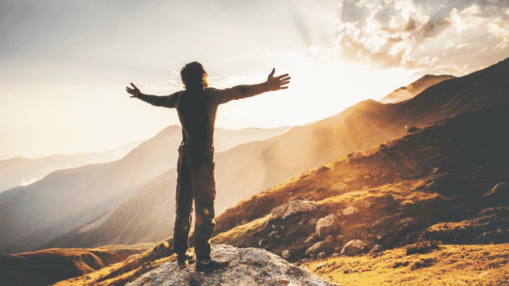 Silhueta de homem com os braços erguidos sob a montanha